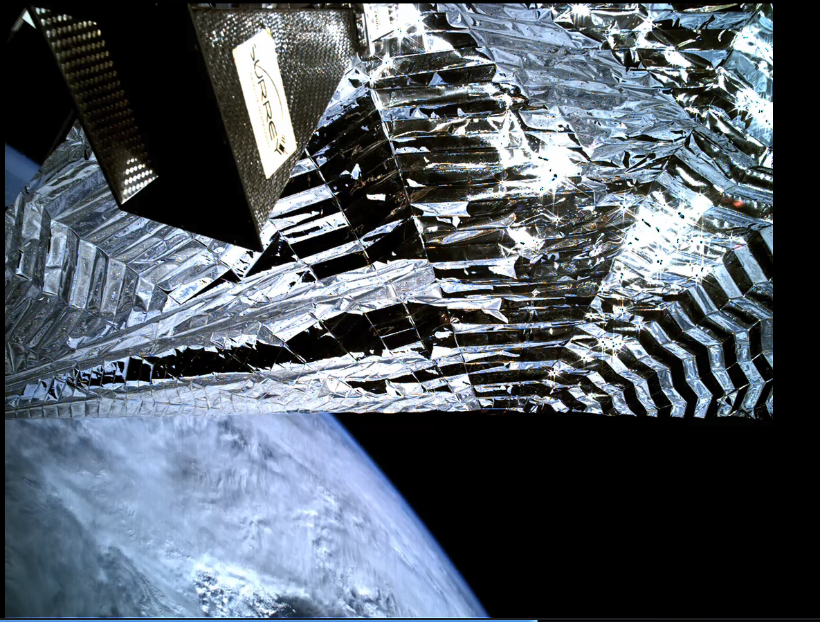 Image acquired by the inspection camera on board TechDemoSat-1 showing the Icarus-1 sail deployed with a view of Earth beyond.  The equipment top left is the satellite's Antenna Pointing Mechanism. Credit SSTL.