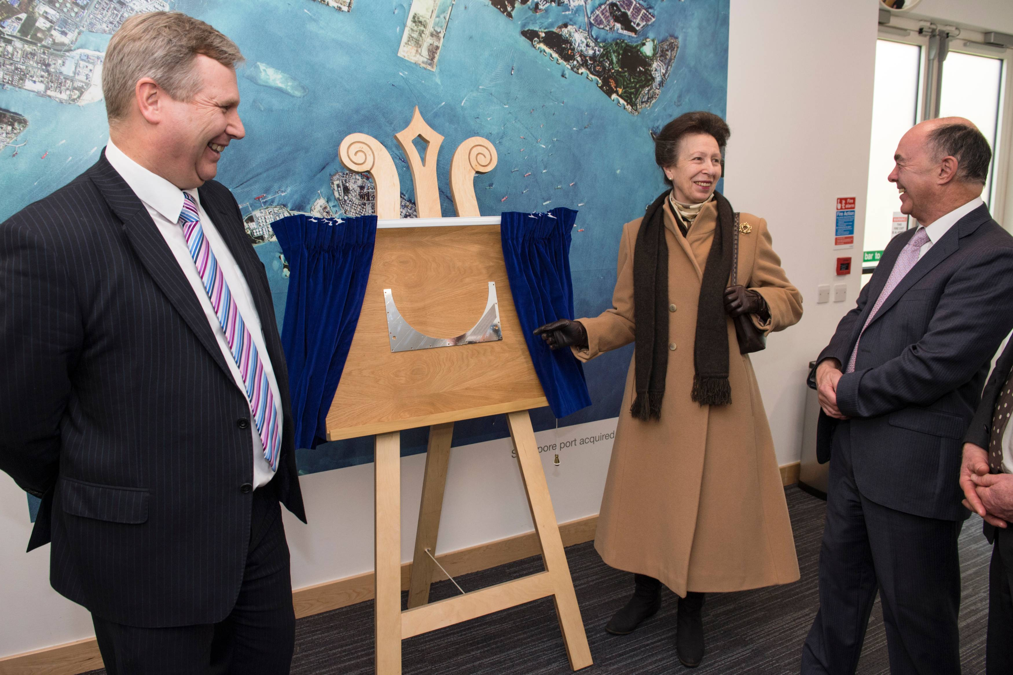 The Princess Royal unveils an engraved plaque commemorating her visit, with Patrick Wood (left) and Sir Martin Sweeting (right).  The plaque is part of the mechanical structure of a satellite that will be launched in 2017.